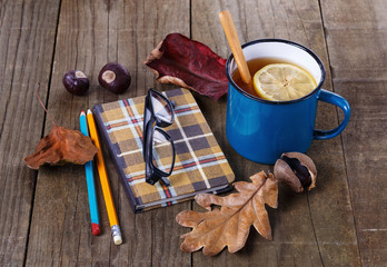 Autumn (fall) cup of tea over rustic wooden background
