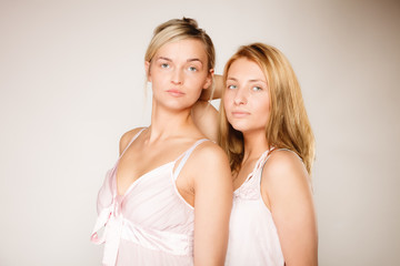 Two blonde women with no makeup on gray