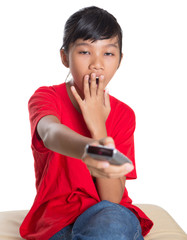 Young Asian girl yawning with television remote control device