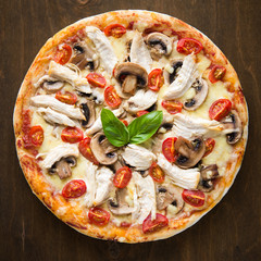 Pizza with chicken, tomato and mushrooms top view