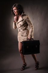 woman wearing a raincoat and holding  suitcase