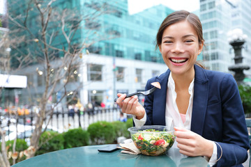 Business woman eating salad on lunch break