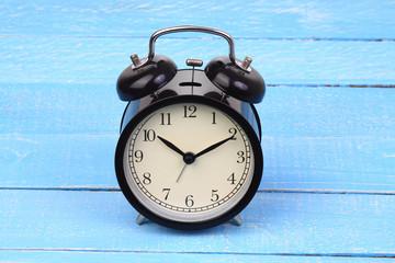 Classic alarm clock on blue wood background.