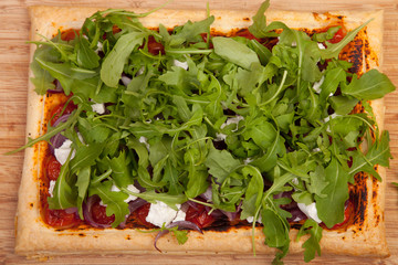 baked puff pastry with tomatos onions and rocket salad
