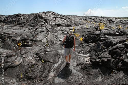 Leinwandbild Motiv Man Hiking on Cooled Lava