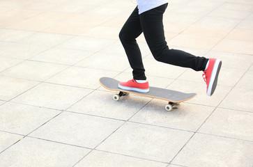 woman legs skateboarding at city