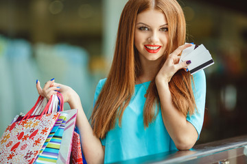 Beautiful girl with a credit card at the mall