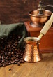 Still life coffee beans in a bag and copper coffee pot