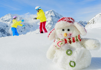 Winter fun, snowman and happy skiers