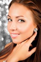 beautiful young woman demonstrates earrings