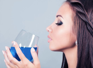 beautiful young woman with a glass of alcoholic drink