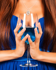 beautiful female hands holding a glass of blue lagoon cocktail
