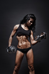sexy young fitness girl posing with dumbbells