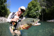 Fly fisherman holding fario trout recently caught - 70880685
