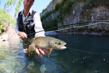 Closeup of fario trout caught in river by fisherman