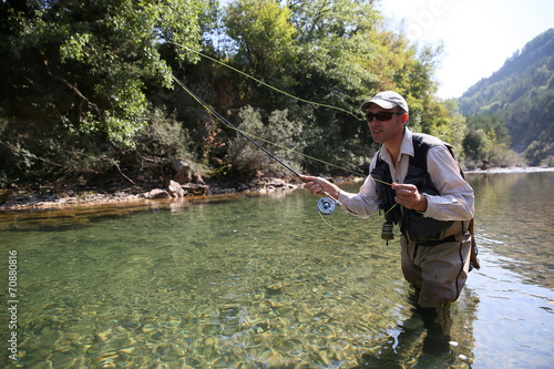 Fotobehang Vissen Closeup of fisherman fly fishing in freshwater river
