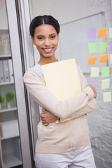 Smiling creative businesswoman holding folder