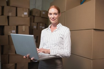 Female manager using laptop in warehouse
