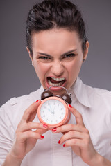Close-up portrait of beautiful girl holding an alarm clock in he