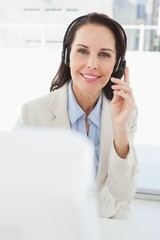 Smiling businesswoman using her headset