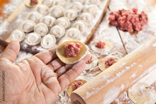 canvas print picture Dumplings. Dough with meat filling on the cook's hands.