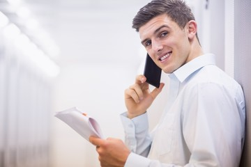 Smiling technician on the phone holding a document