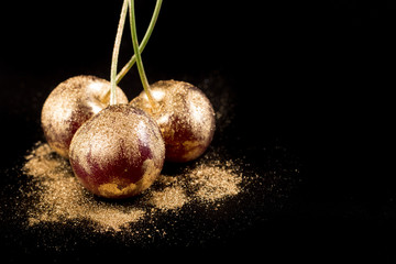 Gold fruits on black background close up