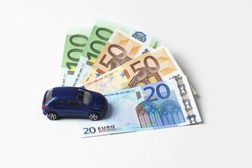 Modellauto und Euroscheine auf weißem Hintergrund