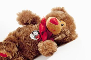 Teddy mit Stethoskop, rote Schleife auf weissem Hintergrund