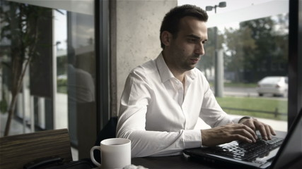 Businessman working on laptop with cup of tea, indoor