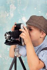 Junge spielt mit nostalgischer Kamera