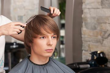Female hairdresser cutting hair of man client.