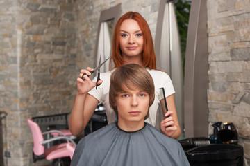 Female hairdresser cutting hair of man client