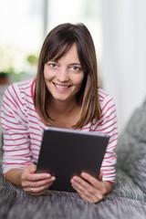 lächelnde frau mit tablet-pc auf dem sofa