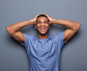 Man laughing with hands on head