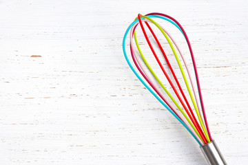 colorful whisk against white distressed wood chopping board.