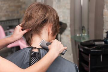 Closeup on female hairdresser cutting hair of man client