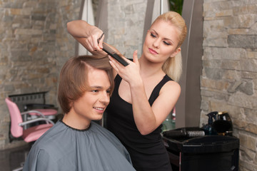 Blond female hairdresser cutting hair of man client.