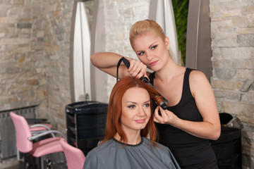 Hairdresser curling red hair with hair irons.