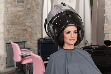 women at hairdresser while drying under hairdryer.