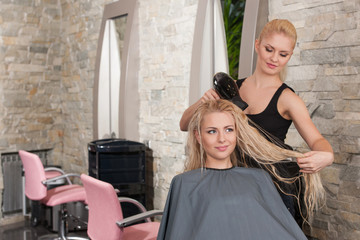 Stylist drying hair of female client at beauty salon.