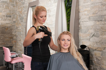 Stylist drying hair of smiling female client at beauty salon.