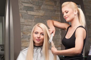 closeup on young woman getting new haircut by hairdresser