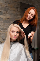 redhead hairdresser applying mousse on client's hair