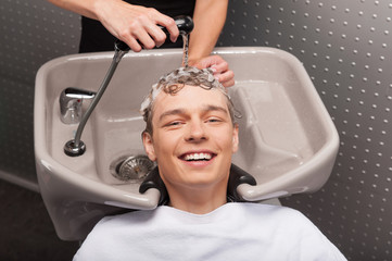 Close-up of young smiling caucasian man having his hair washed.