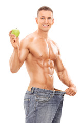 Young man in oversized jeans holding an apple