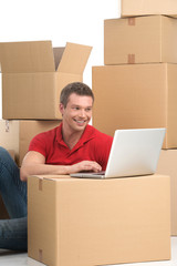 Smiling young man with laptop on box.