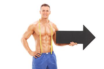 Handsome athlete holding a big black arrow