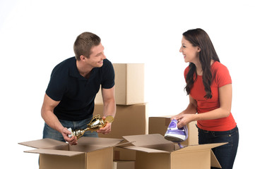 Couple unpacking cardboard boxes in new home.