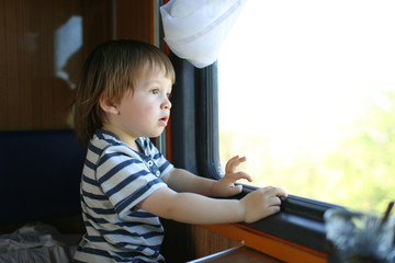 toddler boy looking out of window in the train